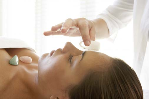 Therapist placing quartz crystal on woman's forehead